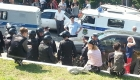 Некоторые из молодых людей принимали солнечные ванны за спинами экипированных полицейских