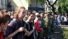 Молодые люди и казаки наблюдают на происходящим на площади