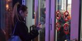 <strong>Девушка, желая войти внутрь торгового центра, показывает полицейским через стекло сообщение, набранное на смартфоне (в итоге её впустили)</strong>