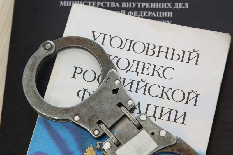 Наручники, уголовный кодекс. Фото с сайта УМВД РФ по Приморскому краю